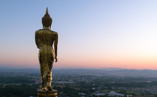 Wielki złoty posąg buddy stojący w wat phra that kao noi rano w prowincji nan tajlandii