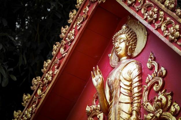 Wielki złoty posąg buddy ze starą czerwoną ścianą i złotą dekoracją na krawędzi dachu.