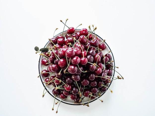 Wielkie dojrzałe czereśniowe jagody z liśćmi na bielu talerzu na białym tle. widok z góry