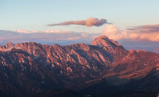 Wielkie dolomitowe góry z drzewami poniżej w codziennym słońcu.