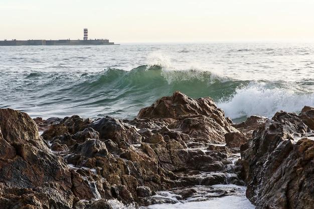 Wielkie fale rozbijające się i pluskające na skałach klify na morzu