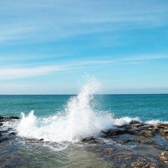 Wielkie fale rozbijające się o brzeg morską pianą