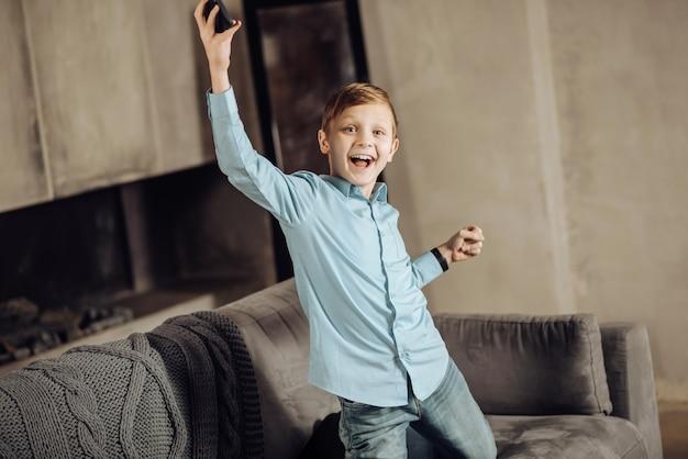Wielkie osiągnięcie. optymistyczny nastoletni chłopiec klęczący na sofie i unoszący ręce w geście triumfu, wygrywając grę na swoim telefonie