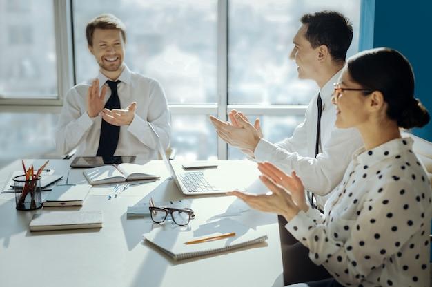 Wielkie osiągnięcie. radośni młodzi biznesmeni siedzą przy stole w sali konferencyjnej i klaszczą w dłonie, świętując zawarcie umowy z nowym sponsorem