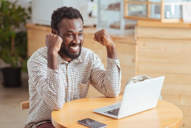 Wielkie osiągnięcie. rozradowany młody człowiek siedzący przy stole w kawiarni i unoszący ręce w geście świętowania, cieszący się dobrą wiadomością, po przeczytaniu wiadomości