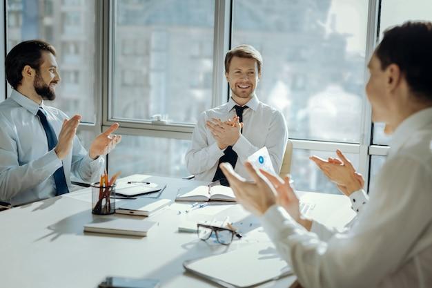 Wielkie osiągnięcie. wesoły młodzi przedsiębiorcy siedzący przy stole w sali konferencyjnej i klaszcząc w dłonie świętując nową umowę z partnerami