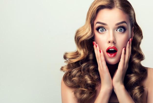 Wielkie rozszerzone oczy, szeroko otwarte usta młodej, zaskoczonej i podekscytowanej kobiety, opowiadającej wyraz twarzy blondynka w szoku