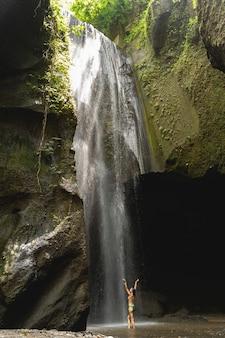 Wielkość natury. urocza brunetka ubrana w strój kąpielowy podczas spędzania wolnego czasu w pobliżu wodospadu