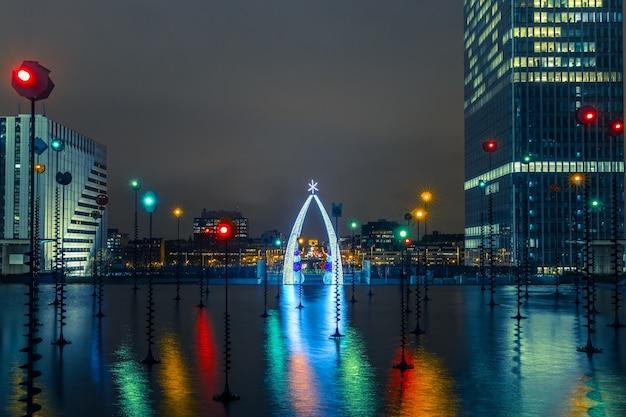 Wielobarwna fontanna w esplanade de la defense w nocy, paryż, francja