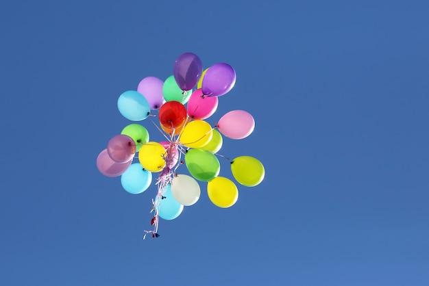 Wielobarwne balony latające na niebieskim niebie