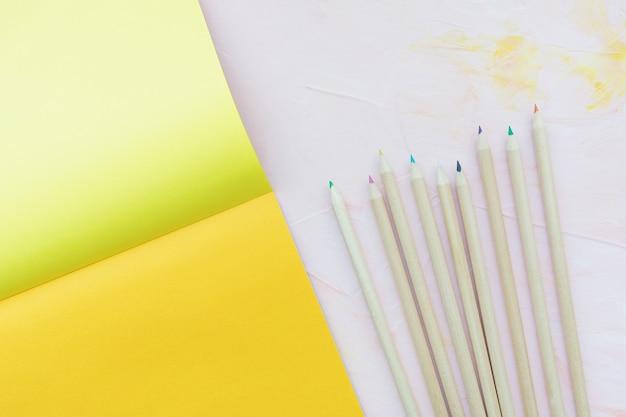 Wielobarwne drewniane ołówki i kartki papieru na różowym, płaskim ułożeniu