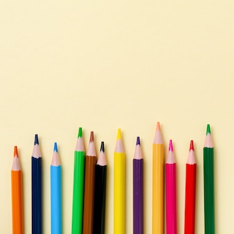 Wielobarwne drewniane ołówki szkolne na żółtej powierzchni papieru. szkolne i biurowe na żółtej powierzchni. koncepcja z powrotem do szkoły. obraz kwadratowy.