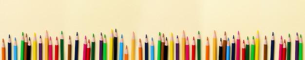Wielobarwne drewniane ołówki szkolne na żółtej powierzchni papieru