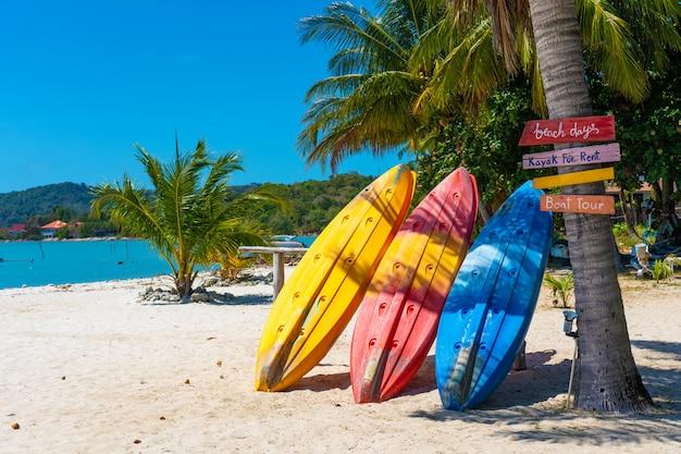 Wielobarwne kajaki na tropikalnej, piaszczystej plaży. wypożyczalnia kajaków. rozrywka turystyczna