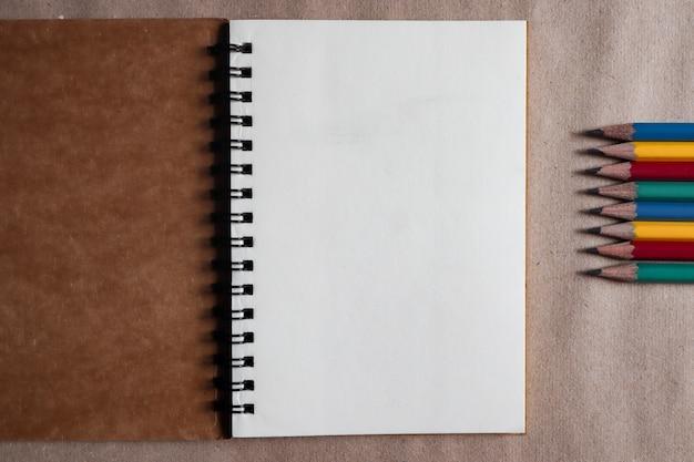Wielobarwne kredki z brązowymi notatkami na brązowym papierze