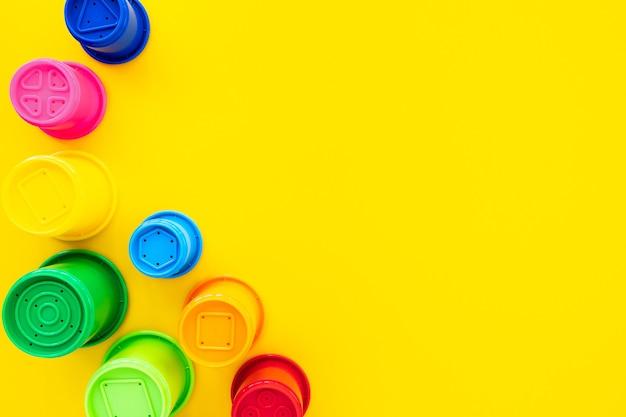 Wielobarwne kształty tęczy dla piasku na żółtym tle. jasne tło dla dzieci, płasko świecki, widok z góry, kopia miejsca na tekst. skład zabawek dla dzieci.