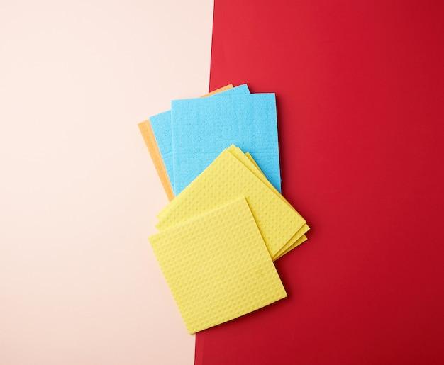 Wielobarwne, kwadratowe gąbki do mycia naczyń na czerwono-beżowym
