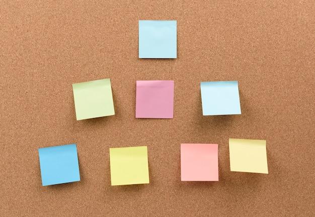 Wielobarwne Kwadratowe Patyczki Są Przyklejone Do Tekstury Brązowego Korka Premium Zdjęcia