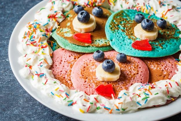 Wielobarwne naleśniki z owocami i bitą śmietaną dla dzieci na białym talerzu. naleśniki z oczami i ustami do jedzenia dla niemowląt.