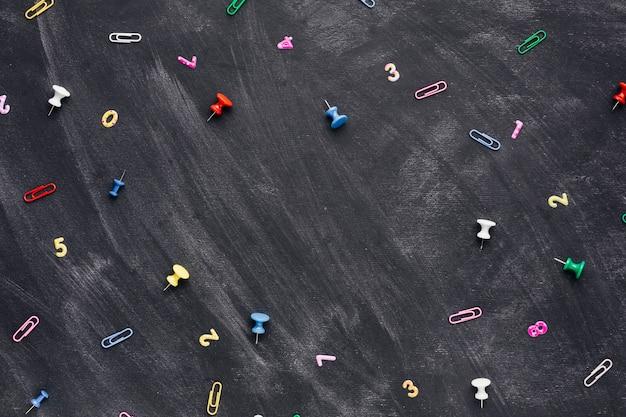 Wielobarwne numery i spinacze z pinezkami rozrzucone na tablicy