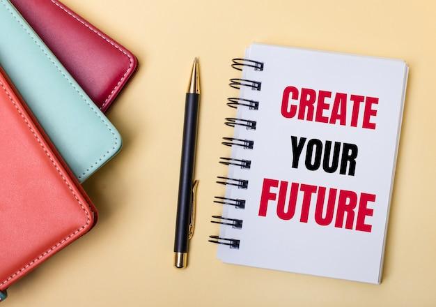 Wielobarwne pamiętniki leżą na beżowej powierzchni obok długopisu i notatnika z napisem stwórz swoją przyszłość