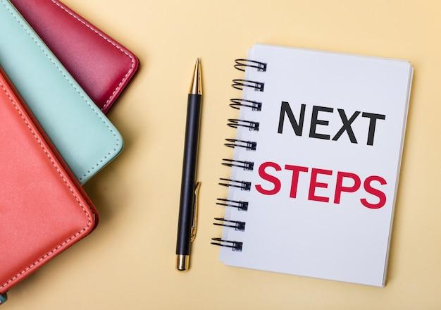 Wielobarwne pamiętniki leżą na beżowej powierzchni obok długopisu i zeszytu z napisem next steps