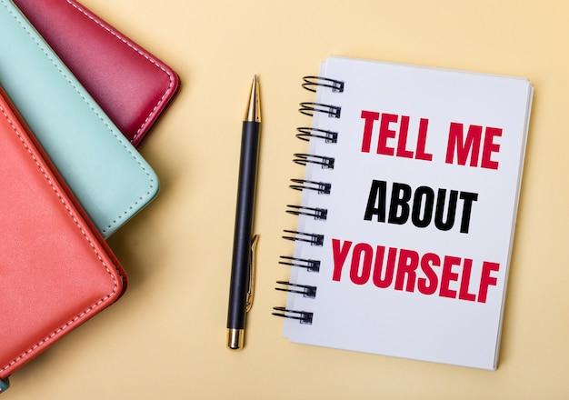 Wielobarwne pamiętniki leżą na beżowej powierzchni obok długopisu i zeszytu z napisem tell me o yourself