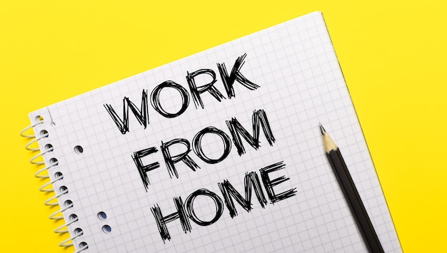 Wielobarwne pamiętniki leżą na beżowej powierzchni obok długopisu i zeszytu z napisem work from home