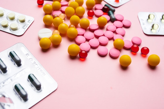Wielobarwne pigułki lek przeciwbólowy różowe tło