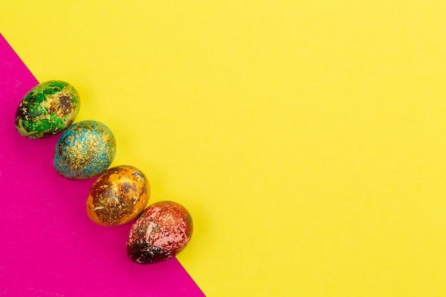 Wielobarwne pisanki w kolorze czerwonym, zielonym, niebieskim, żółtym leżą w rzędzie. malowane pisanki na żółto-różowym tle. leżał płasko. skopiuj miejsce