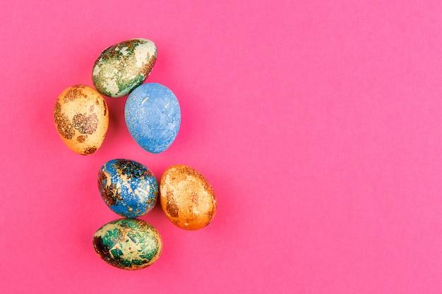 Wielobarwne pisanki w kolorze niebieskim, żółtym i zielonym ze złotem leżą na różowym tle. skopiuj miejsce