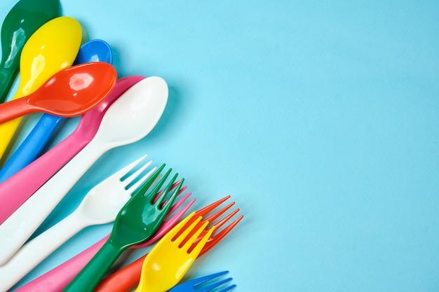 Wielobarwne plastikowe naczynia na niebieskiej przestrzeni. koncepcja zanieczyszczenia środowiska przez plastik, ekologiczne miejsce na tekst, płaskie układanie