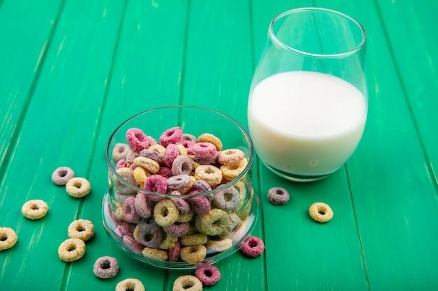 Wielobarwne płatki zbożowe na szklanej misce ze szklanką mleka na zielonej powierzchni