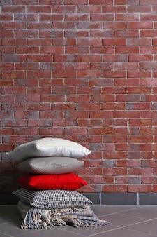 Wielobarwne poduszki na tle ceglanego muru