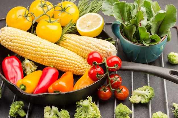 Wielobarwne pomidory, gałązka rozmarynu, kukurydza i papryka na patelni.