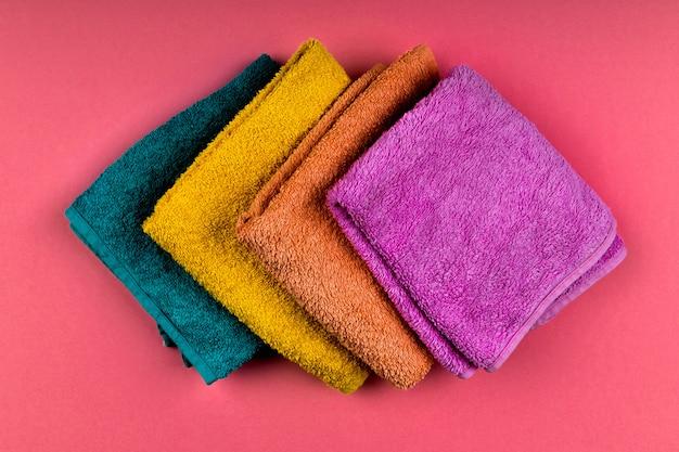 Wielobarwne ręczniki na przestrzeni. różowe, beżowe, żółte i niebieskie ręczniki kwiatowe. miejsce do pisania. zamówienie domu. leżał płasko.