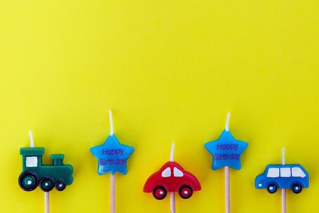 Wielobarwne samochody świec na żółtej powierzchni z miejscem na tekst