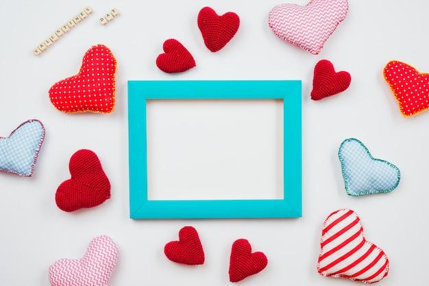 Wielobarwne serca i niebieska ramka są rozmieszczone na białym tle. motyw na walentynki. miejsce na tekst