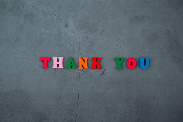 Wielobarwne słowo dziękuję składa się z drewnianych liter na szarej otynkowanej ścianie.
