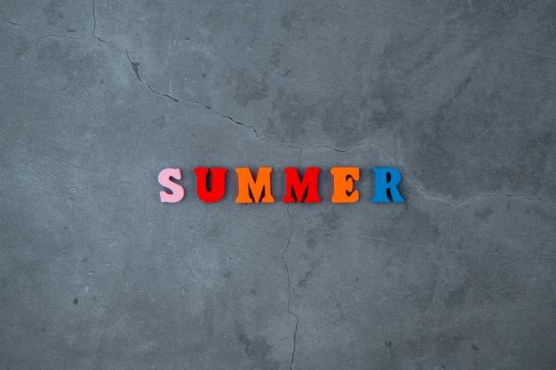 """Wielobarwne słowo """"lato"""" składa się z drewnianych liter na szarej otynkowanej ścianie."""
