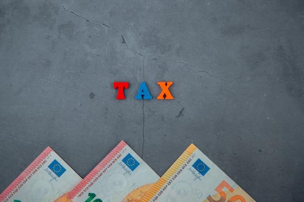 Wielobarwne słowo podatkowe składa się z drewnianych liter na szarej otynkowanej ścianie.