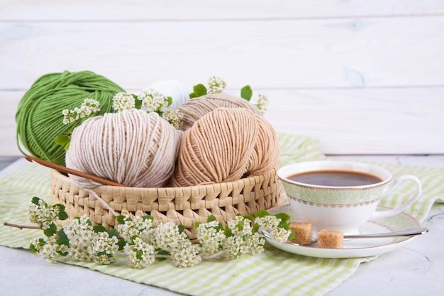 Wielobarwne sploty przędzy w wiklinowym koszu na stole. herbata w pięknej białej filiżance. japoński styl wabi sabi. domowy komfort, rękodzieło.
