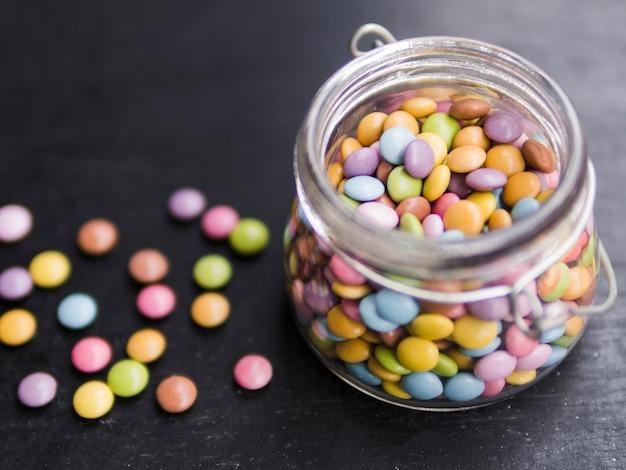 Wielobarwne szkliwione cukierki w szklanym słoju