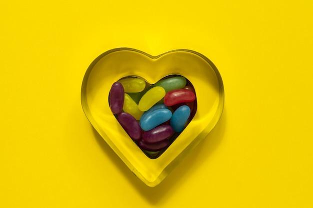 Wielobarwne szkliwione galaretki słodycze w sercu ciasteczka pleśni na żółtym tle z miejsca na kopię.