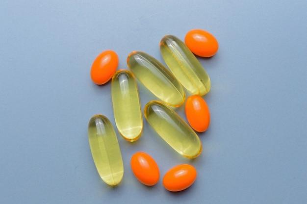 Wielobarwne tabletki i witaminy w kapsułkach na szarym tle. widok z góry