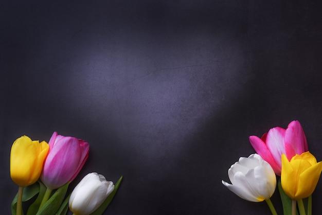 Wielobarwne tulipany i serce na tle ciemnoszarej ściany.