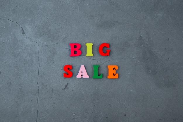 Wielobarwne wielkie słowo sprzedaży jest wykonane z drewnianych liter na szarej otynkowanej ścianie.