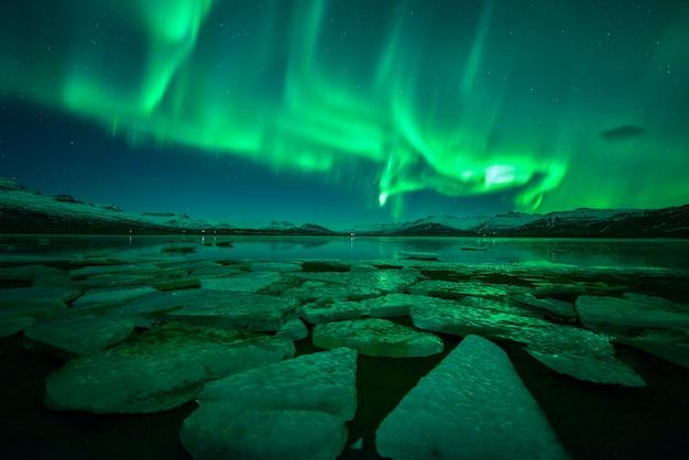 Wielobarwne zorza polarna nad lodową laguną (aurora borealis), piękna zielona zorza tańcząca z gwiazdą w nocy, islandia