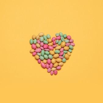 Wielobarwny cukierki w kształcie serca na żółtym tle