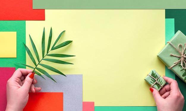 Wielobarwny geometryczny papier warstwowy z kopią. zero marnotrawstwa pomysłów na prezent. twórcze ułożenie płaskie, ręce trzymają liść palmowy i pudełko upominkowe związane sznurkiem i ozdobione zimozielonymi.